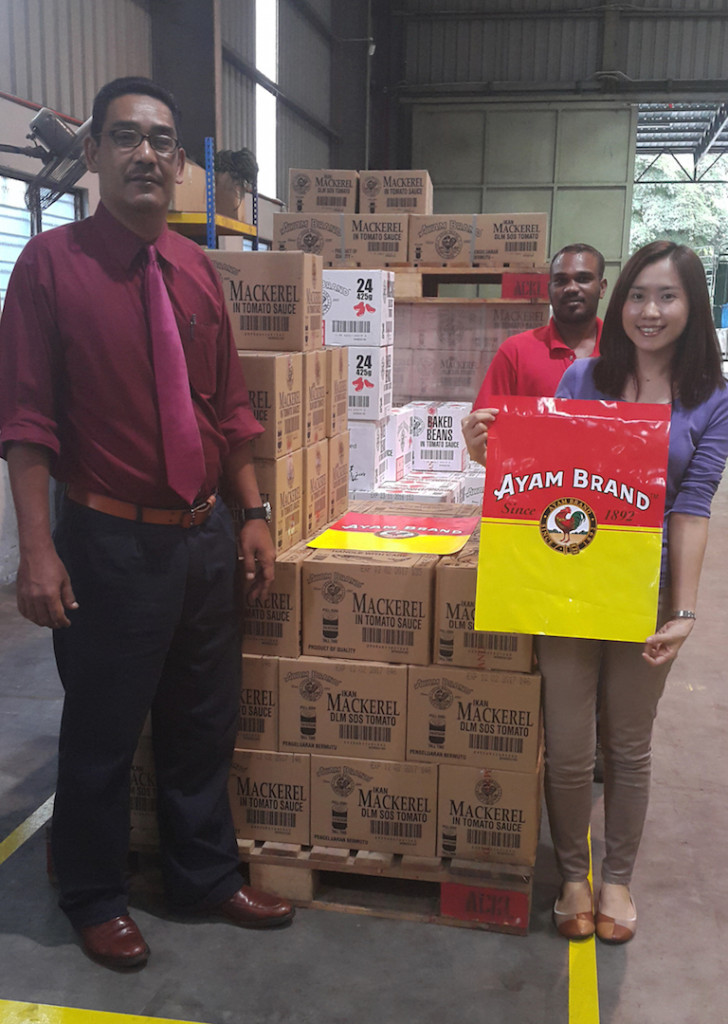 Ayam Brand Human Resources Manager, Encik Mohd Daud Hj Ibrahim (left) with his team consolidating Ayam Brand products to aid flood victims