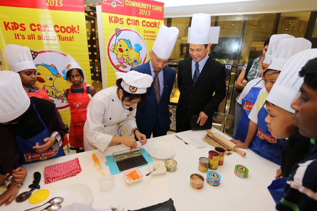 Celebrity Chef Loke, demonstrating to Tunku Dato' Mu Tamir Tunku Tan Sri Mohamed, Chairman of Ayam Brand, and Mr. Ting Seng Hee, CEO of Ayam Brand, the easy way of how to prepare Ayam Brand Tuna Sushi roll, with a simple device made by Ayam Brand at the Ayam Brand Kids Can Cook workshop.
