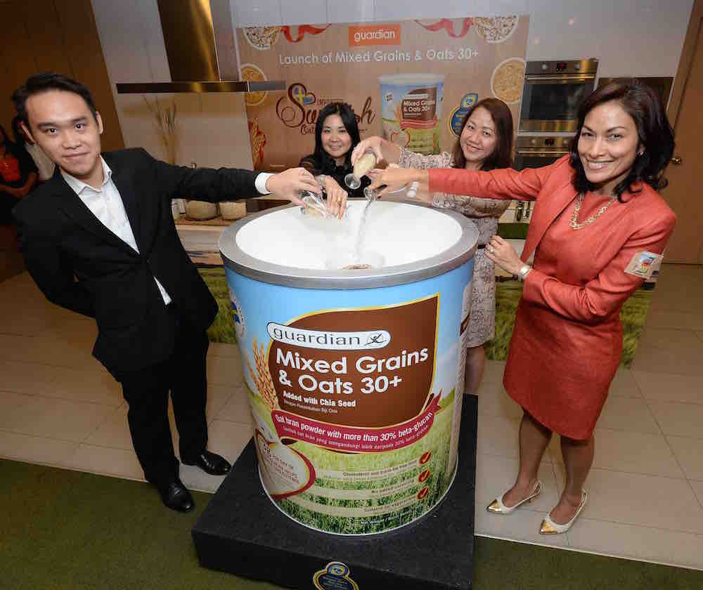 Mr Loh Yen Hon, Head of Health, Guardian Malaysia, Ms. Cheryl Young, Corporate Brand Marketing Manager, Group Health & Beauty Private Label, The Dairy Farm Group, Ms. Elyse Lee, Senior Regional Business Manager, Group Health & Beauty Private Label, The Dairy Farm Group and Ms. Indra Balaratnam, Founder and Consultant Dietitian, The Food Expert Clinic pouring the four featured ingredients chia seeds, barley, brown rice and oat brans to the Guardian Mixed Grains & Oats 30+
