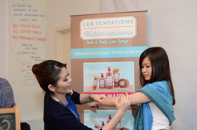 Ms Evelyn Tay (left) showing the correct step on how to use Les Tentations Méditerranéennes body scrub