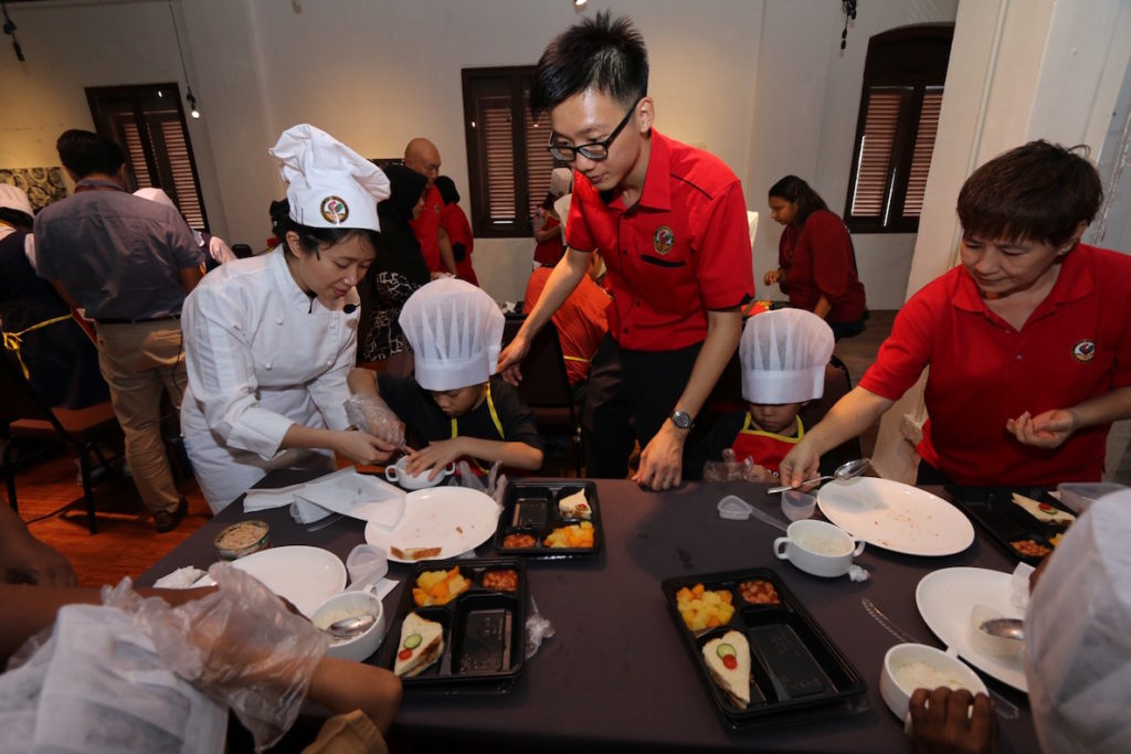 Getting involved, Nicholas and Chef Loke giving a hand to the participants of #AyamBrandCSR