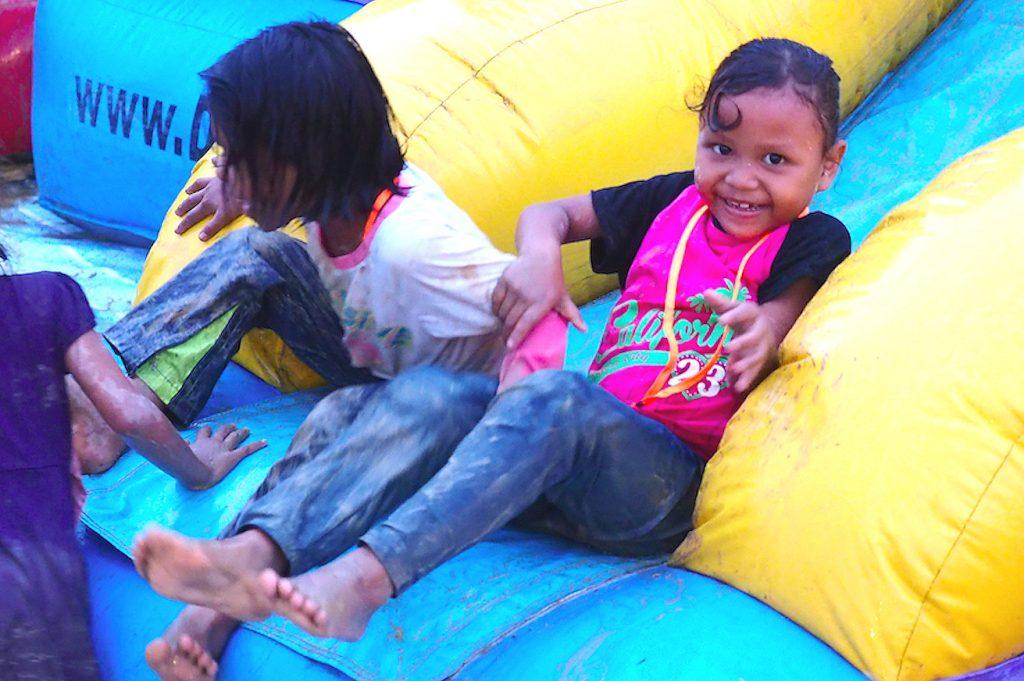 Children from the Orang Asli Sungai Lebak settlement enjoyed the inflatable funfair games despite the rain.