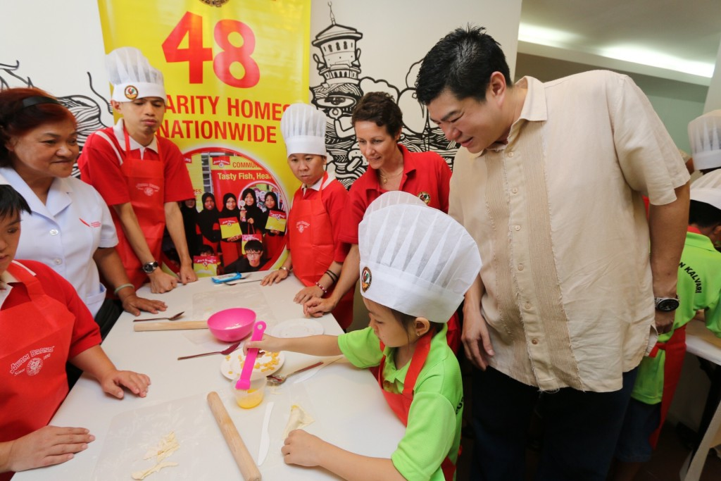 Ms Marie-Magali Falcoz, Ayam Brand Representative (right in red) with Mr Raymond Choong, Home Director, Rumah Berkat ( right) observing the children from Calvary Home during Kids Can Cook Campaign.